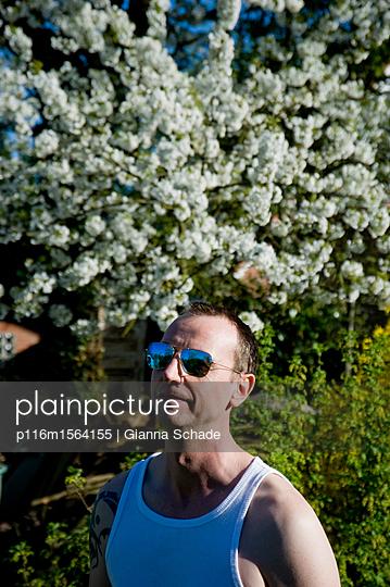 Mann mit Sonnenbrille im Garten - p116m1564155 von Gianna Schade