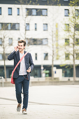 Businessman walking in the city with cell phone and earphones - p300m2104171 by Uwe Umstätter
