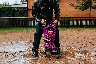 Father playing with toddler girl in puddle - p312m2239401 by Jennifer Nilsson