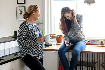 Mother talking with happy daughter using smart phone in kitchen - p426m1179610 by Maskot