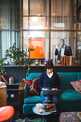 Full length of confident female entrepreneur using laptop sitting on sofa at office - p426m2088944 by Maskot