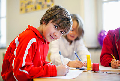 Portrait of smiling boy studying with friends in the background - p426m663161f by Maskot