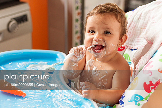 baby stained with yogurt while eating yogurt in his high chair to eat - p1166m2090655 by Cavan Images