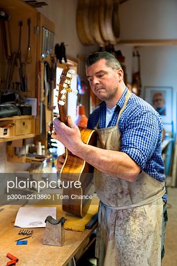 Guitar maker in his workshop - p300m2213860 by Tom Chance