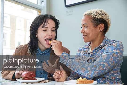 Smiling woman feeding food to girlfriend sitting in cafe - p300m2290782 by Pete Muller