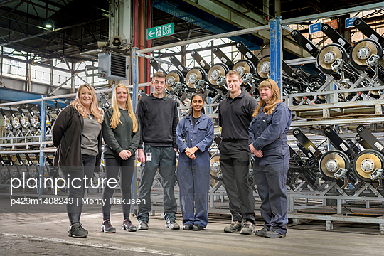 Group portrait of male and female apprentices in car factory - p429m1408249 by Monty Rakusen