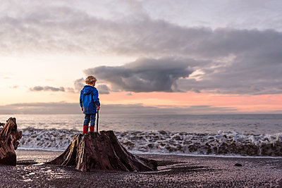 Curly haired boy standing on stump at beach - p1166m2137180 by Cavan Images