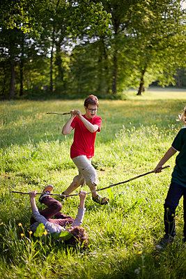 Kinder spielen Stockkampf im Park - p1195m1138157 von Kathrin Brunnhofer