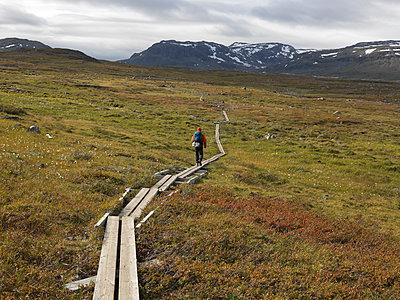 Hiker walking on trail in Lapland - p1216m2184541 von Céleste Manet