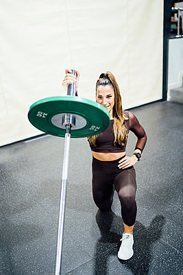 Woman exercising with barbell in gym - p300m2166879 von Oscar Carrascosa Martinez
