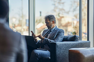 Businessman using laptop and smartphone in hotel lobby - p300m2170931 by Zeljko Dangubic