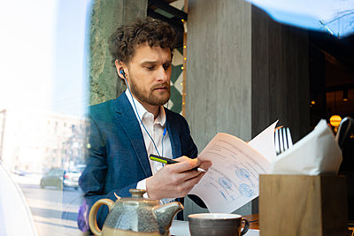 Businessman with in-ear headphones checking strategy while sitting at cafe - p300m2268296 by Vasily Pindyurin
