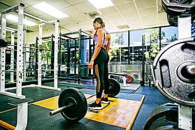 Mixed Race woman standing over barbell in gymnasium - p555m1304144 by Peathegee Inc