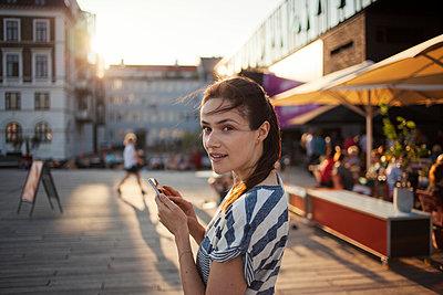 Junge Frau benutzt ihr Smartphone, Kopenhagen, Dänemark - p586m940586 von Kniel Synnatzschke