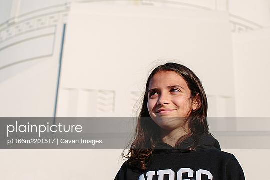 Twelve year old girl wearing a hoodie smiles while looking away - p1166m2201517 by Cavan Images