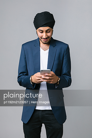 Young Indian businessman wearing turban, using smart phone - p1192m2123267 by Hero Images