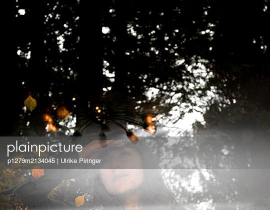 Frau sieht durch eine Fensterscheibe - p1279m2134045 von Ulrike Piringer