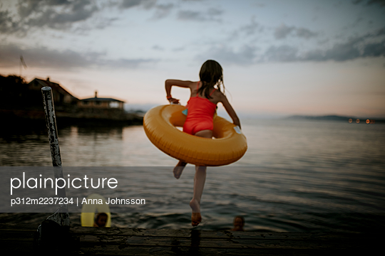 Girl with inflatable ring jumping into water - p312m2237234 by Anna Johnsson