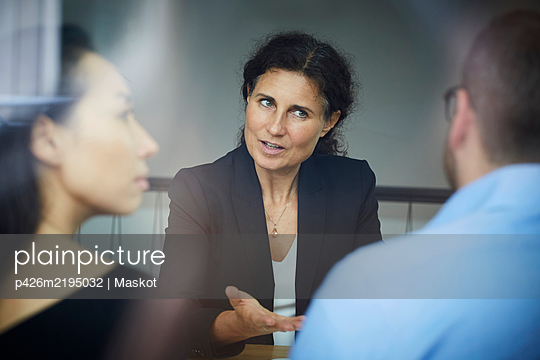 Confident mature female financial advisor discussing with businessman and businesswoman during meeting at office - p426m2195032 by Maskot