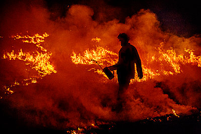 Firefighter with a drip torch walks through a wildfire in Australia - p1166m2193727 by Cavan Images