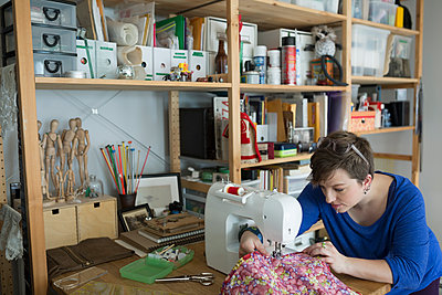 Seamstress using sewing machine in home office - p1192m1127960f by Hero Images