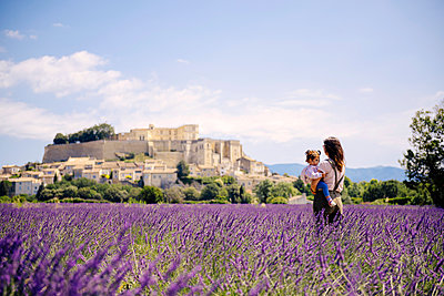 France, Grignan, mother standing in lavender field with little daughter on her arms looking at village - p300m2070241 by Gemma Ferrando