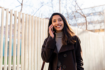 Smiling young woman on the phone in the city - p300m2166189 by VITTA GALLERY