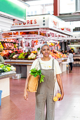 Portrait of smiling woman buying groceries in a market hall - p300m2179903 by VITTA GALLERY