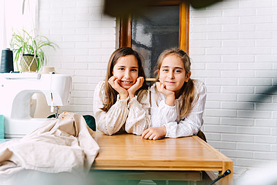 Portrait of two girls leaning on table with sewing machine at home - p300m2188531 by Eloisa Ramos