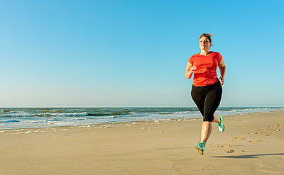 Mature woman running on a beach at sunset - p429m1155622 by Mischa Keijser
