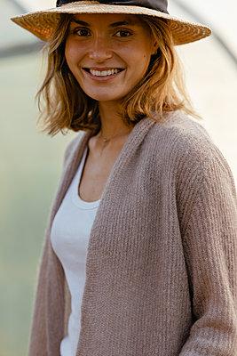 Junge Frau mit Hut lächelt in die Kamera - p432m2293175 von mia takahara