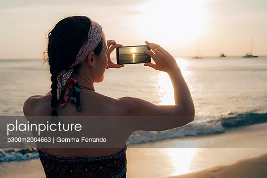 Thailand, Koh Lanta, woman on the beach taking photo with cell phone at sunset - p300m2004663 von Gemma Ferrando