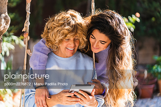Smiling mother using digital tablet while sitting on swing by daughter at front yard - p300m2276872 by Manu Padilla Photo