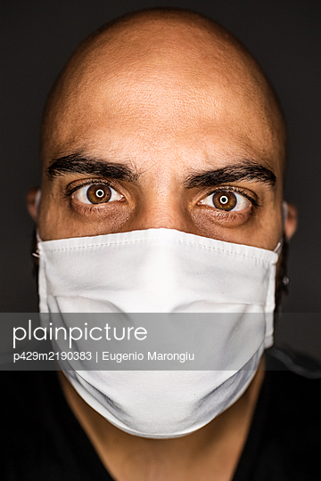 A man wearing a face mask covering his nose and mouth.  - p429m2190383 by Eugenio Marongiu