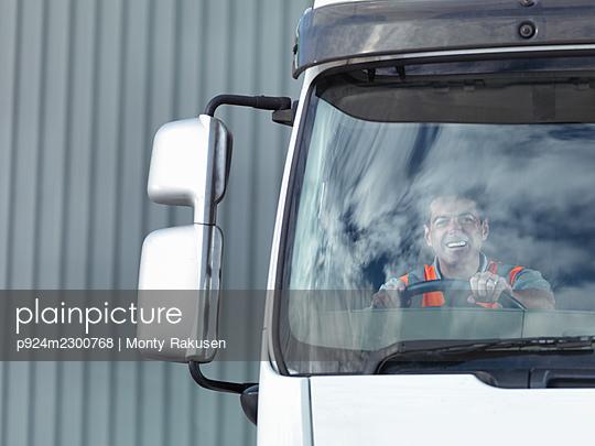 UK, Portrait of smiling truck driver in truck cabin - p924m2300768 by Monty Rakusen