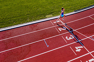 Aerial view of a running young female athlete on a tartan track crossing finishing line - p300m2132532 by Stefan Schurr