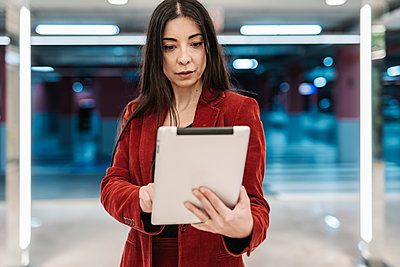 Beautiful mature businesswoman using digital tablet against illuminated lights at subway station - p300m2266398 by COROIMAGE