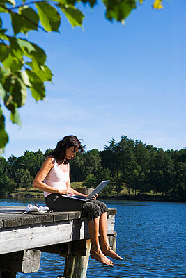 A woman with a laptop on a jetty by a lake Sweden. - p31221231f by Plattform