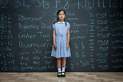 Portrait of schoolgirl standing in front of large chalkboard with schoolwork chalked on it - p429m1181119 by Ian Nolan