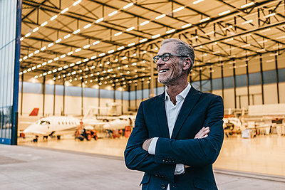 Mature businessman in front of hangar - p586m1208531 by Kniel Synnatzschke