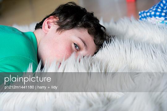Junge auf dem Fellteppich - p1212m1441180 von harry + lidy