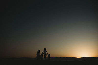 Silhouette of four young sisters at beach during sunset - p1166m2165911 by Cavan Images