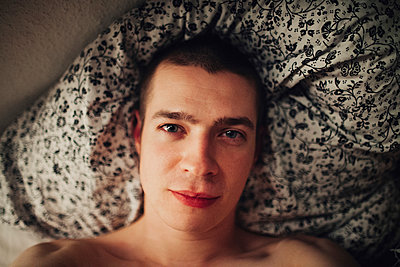 Young man in bed - p1184m992508 by brabanski