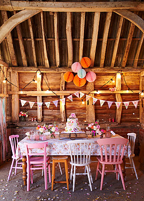 PInk chairs and tiered cake with bunting and lights in wood cabin  late summer  UK - p349m2167851 by Sussie Bell