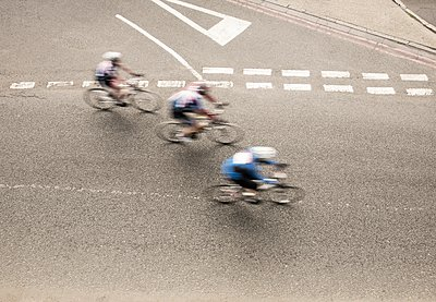 Overhead view of three cyclists speeding on urban road in racing cycle race - p429m1118477f by Seb Oliver
