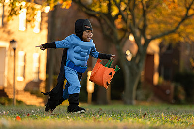 African American boy trick-or-treating on Halloween - p555m1413661 by Roberto Westbrook