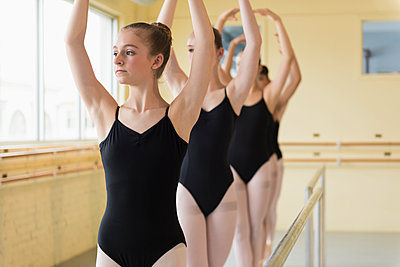 Girls standing with arms raised near barre in ballet studio - p555m1491092 by Mark Edward Atkinson