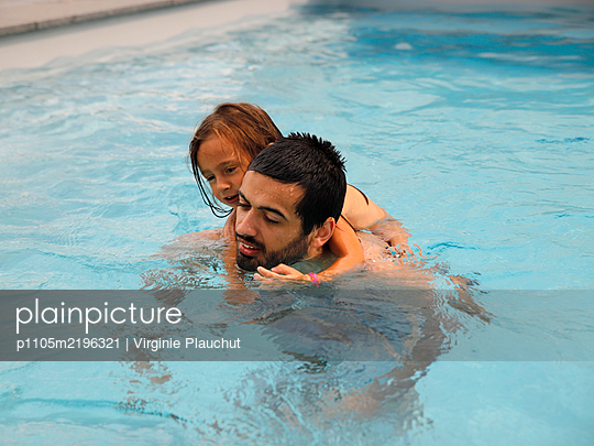 Father and daughter in the pool - p1105m2196321 by Virginie Plauchut