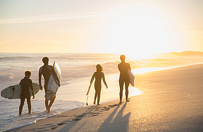 Family surfers walking with surfboards on sunny summer sunset beach - p1023m1506546 by Sam Edwards