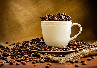 Coffee beans in cup and saucer - p1427m2038472 by Tetra Images